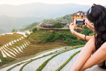 Tourist taking picture of rice terrace landscape with a phone
