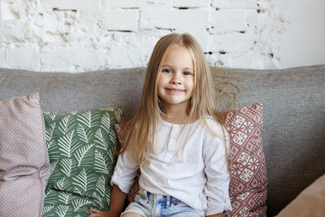 Positive beautiful little girl of European appearance sitting on comfortable sofa in living room, surrounded with decorative pillows, looking at camera and smiling happily. Childhood concept