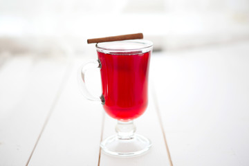 Mulled wine with cinnamon sticks on a white wooden background