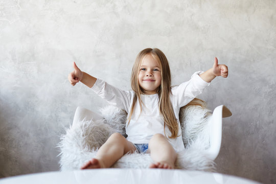 Portrait of charming happy little girl with bare feet and long straight hair sitting on white armchair, showing thumbs up with both hands as sign of approving and liking good idea. Body language