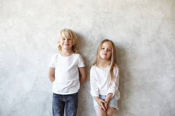 Puppy love, relationships and childhood. Isolated studio portrait of sweet little girl and blonde cute boy in love standing side by side at blank wall, having shy looks, not talking to each other