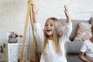 Portrait of adorable pretty female child exclaiming and gesturing excitedly, raising arms up as she gave right answer on zagadka and now will receive some prize, feeling happy and proud of herself