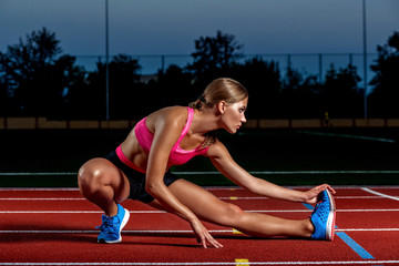 Attractive young woman athlete stretching legs on stadium