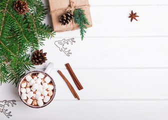 Hot chocolate, fir branches and Christmas gift on white background