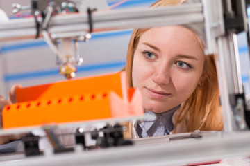 Wall Mural - A female student or laboratory assistant in the automation laboratory is debugging the work of the 3d printer. 3d printer is a device for modeling 3D objects