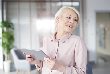 Businesswoman with digital tablet laughing .