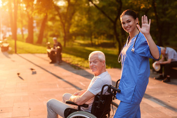 A nurse is greeting someone. Behind her in the wheelchair sits an old man and smiles