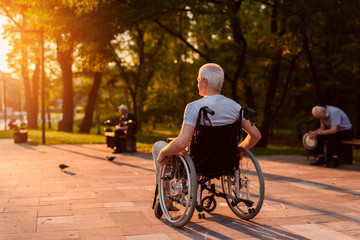 A lonely old man who sits in a wheelchair looks at a beautiful sunset in the park