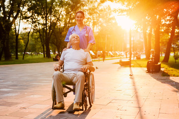 An old man who sits in a wheelchair and a nurse stand in the park at sunset