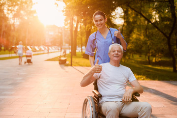 Nurse and old man who sits in a wheelchair showing a thumbs up in the park at sunset
