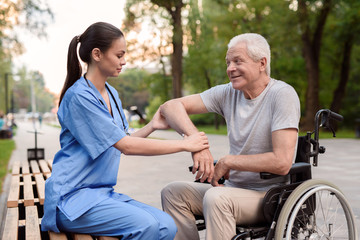 A nurse carefully examines the elbow of an elderly patient on a bench in the park