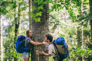 Hiking couple. Young couple with backpacks hugging tree and having fun