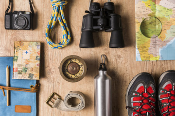Overhead view of travel equipment for a backpacking trip on wooden floor. Adventure travel concept.