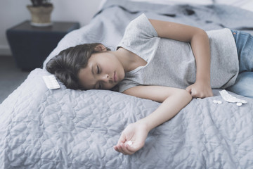 The girl took a large dose of tablets and lies on the bed next to the opened packing of tablets