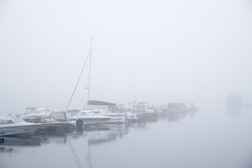 Boats in a foggy harbour in Kuopio, Finland