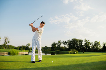 An athlete in a white suit took a golf club to strike