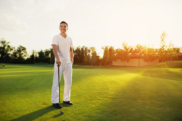 A professional golfer. A man is posing on a golf course with a stick in his hand