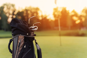 Close up. A bag for golf clubs with golf clubs on the sunset background
