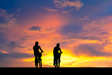 Silhouette image. Shadow of woman riding bike.