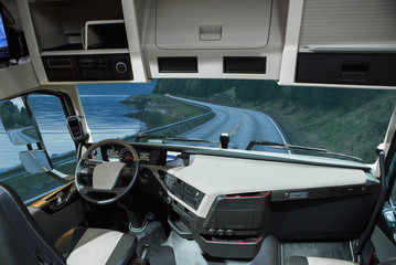 Self driving truck without driver on a road. Inside view.