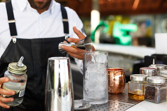 barman pouring alcohol in a glass