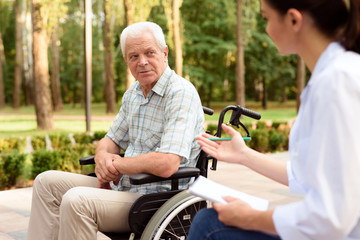 An elderly man in a wheelchair at a doctor's reception in a summer park