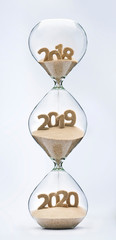 Passing into New Year 2019, 2020. Past, present and future concept. 3 part hourglass. Falling sand taking the shape of years 2018, 2019 and 2020.