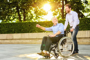 A man is walking in the park with his father, who is sitting in a wheelchair. The man and the old man are happy