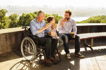 The old man in a wheelchair, his son and his grandson eat in the park