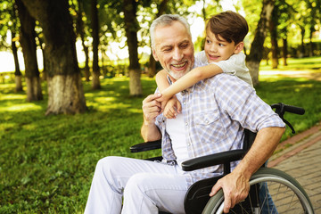 The boy and his grandfather are walking in the park. The old man is sitting on a wheelchair. The boy is hugging the old man