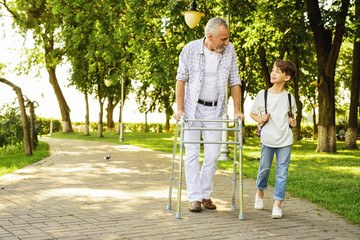 A boy and an old man on stilts for adults are walking in the park