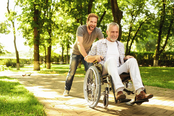 A pensioner on a wheelchair and his adult son are walking around the park. They are happy and have fun