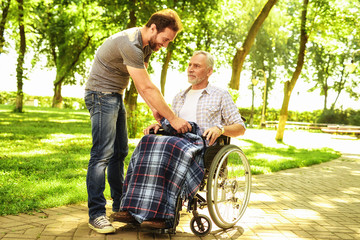 A man and an old man in a wheelchair in the park. The man covered the old man with a rug