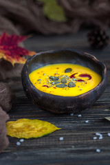 Homemade pumpkin cream soup with pumpkin seeds and pumpkin oil on a dark background