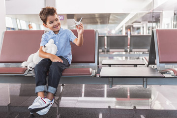 Interested smiling male child locating at terminal