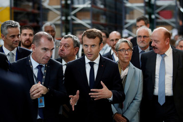 French President Emmanuel Macron speaks Amazon French Operations Director Ronan Bole during a visit at the Amazon factory in Boves
