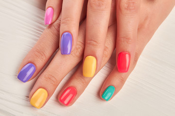 Foto auf Leinwand Maniküre Female fingers with colorful nails. Beautiful woman hands with pastel colors nails on white wooden background. Well-groomed hands with summer manicure.