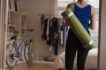 Mid section of woman carrying exercise mat