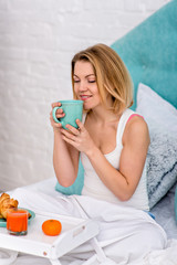 A young blond girl enjoys the aroma of coffee. Breakfast in bed