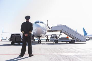 Aviator glancing at big aircraft