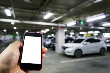 hand using mobile smart phone with blurred image of indoor car parking garage area, RFID solution management system, internet, social media and car parking sensor technology concept