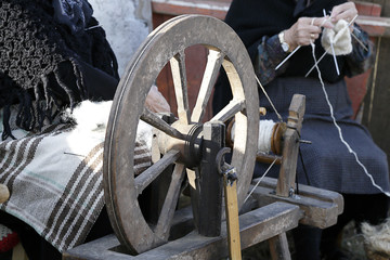 In the foreground an old spinning wheel in the background, out of focus, a woman knitting