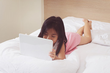 Asian little girl using tablet computer in bed