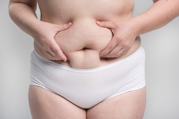 Woman pinching her stomach