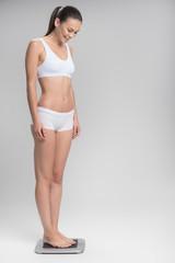 Joyful skinny girl standing on scales