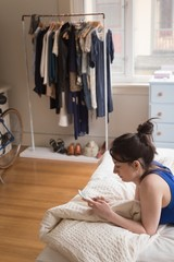 Side view of woman using phone on bed