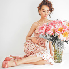 Beautiful young woman with big bouquet of peony