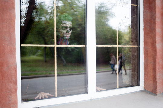 View of man with skeleton make up in the window. Halloween makeup concept, scary man in window.