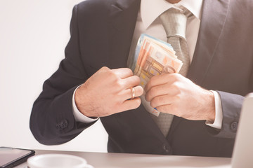 Money in pocket, businessman putting euro banknotes in suit pocket, bribe and corrupution concept.
