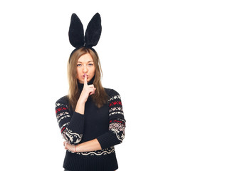 Woman lips and a finger. Funny woman in a bunny suit. Woman in a winter sweater. Woman on a white background. Winter concept of advertising information. Christmas mood. Rabbit woman. Finger on lips.